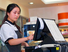 Photo of young café barista at cash register