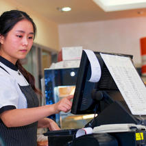 Photo of young café barista at cash register