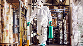 Image of man in protective suit and mask disinfecting warehouse full of food products