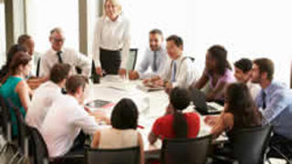 Image of group during company-level meeting around boardroom table