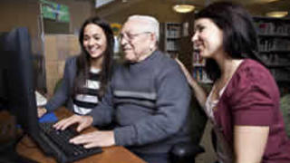 Image of volunteers teaching older man computers